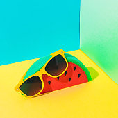 art set with yellow sunglasses and slice of watermelon in bright colors on bold background in the corner.