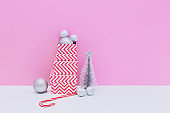 Silver fir tree, decoration balls, three sized gift boxes and candy cane on white and pink background. Christmas and new year concept. Winter holidays composition. Copy space, minimal art