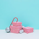 Silver decoration balls, three sized gift boxes and candy cane on white and light blue background. Christmas and new year concept. Winter holidays composition.