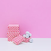 Winter holidays composition. Three sized gift boxes and silver decoration balls on white and light pink background. Christmas and new year concept.