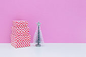 Silver fir tree and gift boxes on white and pink background. Christmas and new year concept. Minimalism, copy space