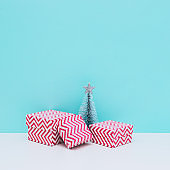 Winter holidays composition. Three sized gift boxes and fir tree on white and blue background. Christmas and new year concept. Minimalism