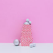 Three sized gift boxes and silver decoration balls on white and light pink background. Christmas and new year concept. Winter holidays composition.