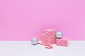 Silver decoration balls, three sized gift boxes and candy cane on white and pink background. Christmas and new year concept. Winter holidays composition. Copy space, minimalism