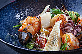 Close up view on salad with seafood served in dark bowl. Food photography for ads or recipe. Copy space. Warm salad with shrimp, squid, scallop, octopus in bowl. Lunch snack.