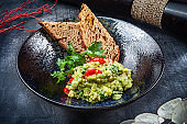 Delicious bowl of Guacamole with bread close up on dark table with copy space. green, naturally made traditional guacamole. Mexican cuisine. Served Appetizer food from avocado