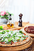 Fresh pizza with prosciutto on a wooden table on light background. Olive oil, pepper, prosciutto and flowers on background. Vertical image with copy space for design.
