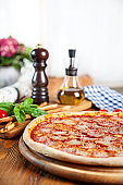Selective focus on pizza with salami and tomato. Fresh homemade pizza with ingridients on background: salami, basil, cherry tomato, olive oil. Image with copy space for desig or logo. Italian cuisine