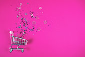 Shopping cart with confetti on magenta background.