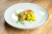 Salmon steak with mango and white sauce on a white plate on a wooden background. Restaurant serving dishes. Delicious seafood dish. Fish. Food photo for menu or recipe