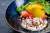 Greek yogurt with olive oil, spices with baked vegetables, bell pepper and tomato in dark bowl. Healthy, vegan food for dieting menu. Food photo background