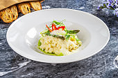 Close up view on tradtional and tasty risotto with parmesan, asparagus and chili. Mediterranean and italian cuisine. Restaurant food for lunch. Flat lay food on marble table. Picture for recipe. vegan