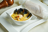 Close up view on fresh homemade Waterzooi soup - stew dish from Belgium. Yellow cream soup mussel and shrimp in white bowl. Restaurant food