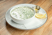 Close up on bowl with okroshka - A cold soup made of kvass or serum with different herbs and finely chopped meat or fish. Russian cuisine. Food photo background fore recipe or menu