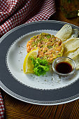 Fresh Salmon tartare, avocado with croutons and soy sauce in white plate on wooden background in composition with red cloth. Copy space. Top view