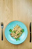 Tagliatelle with chicken, white sauce and parmesan in blue bowl on wooden background. Traditional homemade italian pasta. Close up