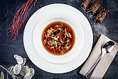 Top view on crab soup served in white plate on dark background. Flat lay food for lunch. Seafood. Reaydy for eat. Picture for recipe. Copy space for design. View from above