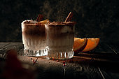 Cold cocktail sprinkled with cinnamon on a dark background. Low key photography. Flying ingridients in glass.