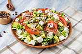Close up view on large plate with tasty salad: tomato, feta cheese, avocado, asparagus and greens. Food photo background. Healthy, dieting, balanced salad