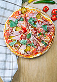 Italian, homemade sliced pizza with meat, salami, cucumber, basil and hot pepper on a wooden table. Top view food with copy space. Flat lay