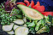 Close up view on green salad with avocado in served in black textured plate on dark background. Flat lay food. Vegan fresh salad. Copy space for design. Selective focus