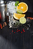 Cocktail making concept. Cold bar utensils with fresh ingridients and ice on dark background.
