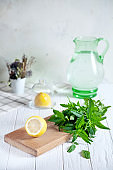 Preparation of the lemonade drink. Cutted lemon on board with fresh mint. Refreshing, cold, summer drink. Lemonade pitcher. Making traditional, healthy lemonade. Ingredients for making mojito