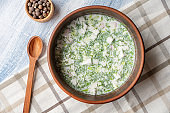 Top view on bowl with okroshka - A cold soup made of kvass or serum with different herbs and finely chopped meat or fish. Russian cuisine. Food photo background fore recipe or menu