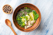 Top view tasty Vietnamese imperial soup with lemon, mint, herbs and buckwheat noodles, fish. Bowl with soup for lunch on blue background. Flat lay food photo. Seafood