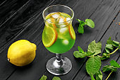Glass of cold green cocktail with lemon and mint. Mojito. Summer freshness lemonade with ice. Dark background. Copy space.
