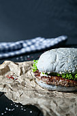 Burger with meat, sauce, salt and vegetables on craft paper. Snack with a blue bun on a dark wooden background with insta tint. Close up view on american fast-food.