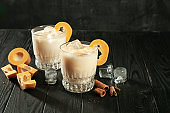 Close up view on white proteinaceous egg, alcohol cocktail in glasses. Glass with ice, pumpkin and cinnamon standing on dark wooden background.