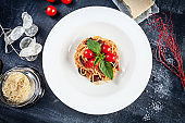 Close up view on traditional italian pasta with basil and cherry tomato in white plate. Flat lay italian cuisine with copy space for design. mediterranean noodle for lunch. Top view