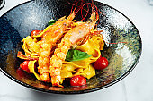 Homemade Italian pasta with cherry tomatoes and seafood. Pasta with fresh and tasty langoustines shrimp in a dark stylish bowl on a marble table. Food photo for menu or recipe. Restaurant