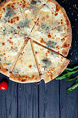 Close up view on pizza with 4 cheeses: gorgonzola and parmesan. feta, mozarella. Selective focus. Slice of pizza with ingridients. Dark background. Italian cuisine. Copy space