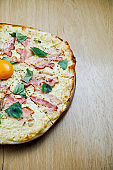 Italian, homemade carbonara pizza with yolk and bacon on a wooden table. Top view food with copy space. Flat lay
