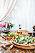 Close up view on fresh served pizza with prosciutto on a wooden table on light background. Pizza with wine. Vertical image with copy space for text.