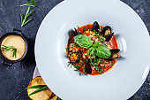 Close up view on tasty seafood soup in white restaurant bowl. bouillabaisse with mussels, salmon and basil with a snack of potatoes with cheese sauce. Dark background. Food photo for menu or recipe