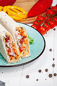 Close up view on traditional Arab shawarma, shaurma or kebab on blue plate stands on white background. Freh doner with ingridients, tomato, spices and bell pepper. Arabic cuisine with copy space