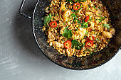 top view on Pad thai, or phad thai stir-fried rice noodle with vegetables and chicken, hot chili pepper and parsley in black bowl on grey stone background. Street pan-asian food with copy space