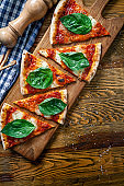 Top view on sliced margarita pizza on wooden cutting board background. Cutted pizza with copy space for design. Picture for menu, italian cuisine