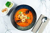 Vietnamese Tom Yum soup with seafood. Red soup with shrimp, scallop, mussels, salmon in a dark stylish bowl on a marble table. Minimalosm food photo concept. bouillabaisse