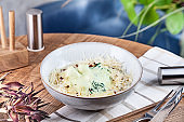 Close up view on Chicken Meatballs in cream sauce with cheese parmesan in bowl. Healthy, dieting, balanced food for lunch. Wooden background. Copy space for design. Horizontal