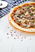 Close up view on pizza on white wooden background with ingridients.  Restaurant, food menu, recipe, cafe concept. Lifestyle food. Italian cuisine with free copy space.