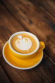 Hot cappuccino coffee in a yellow cup with latte art on wooden table