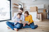 A young family with a toddler girl moving in new home, using tablet.