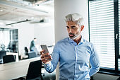 Mature businessman with smartphone standing in an office, taking selfie.