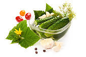 Freshly-salted cucumbers with black currant leaves, garlic and dill in salt marinade (ukrainian recipe), isolated on white background.