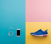 A studio shot of running shoes and smartphone on color background. Flat lay.