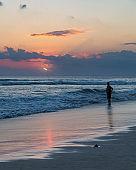 Beatiful sunset and silhouette of a man on Seminyak beach, Bali